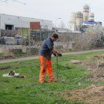 Archeoloog zet een boring nabij het industrieterein