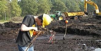 Archeoloog bekijkt een boormonster tijdens een archeologische begeleiding.