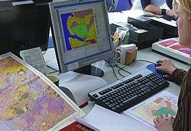 Voor het bureauonderzoek bestudeert de archeoloog verschillende kaarten achter de computer.