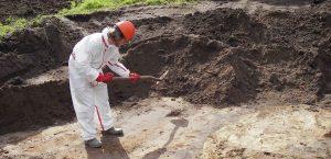 Archeologen werken bij een begeleiding in vervuilde bodems met saneringspakken.