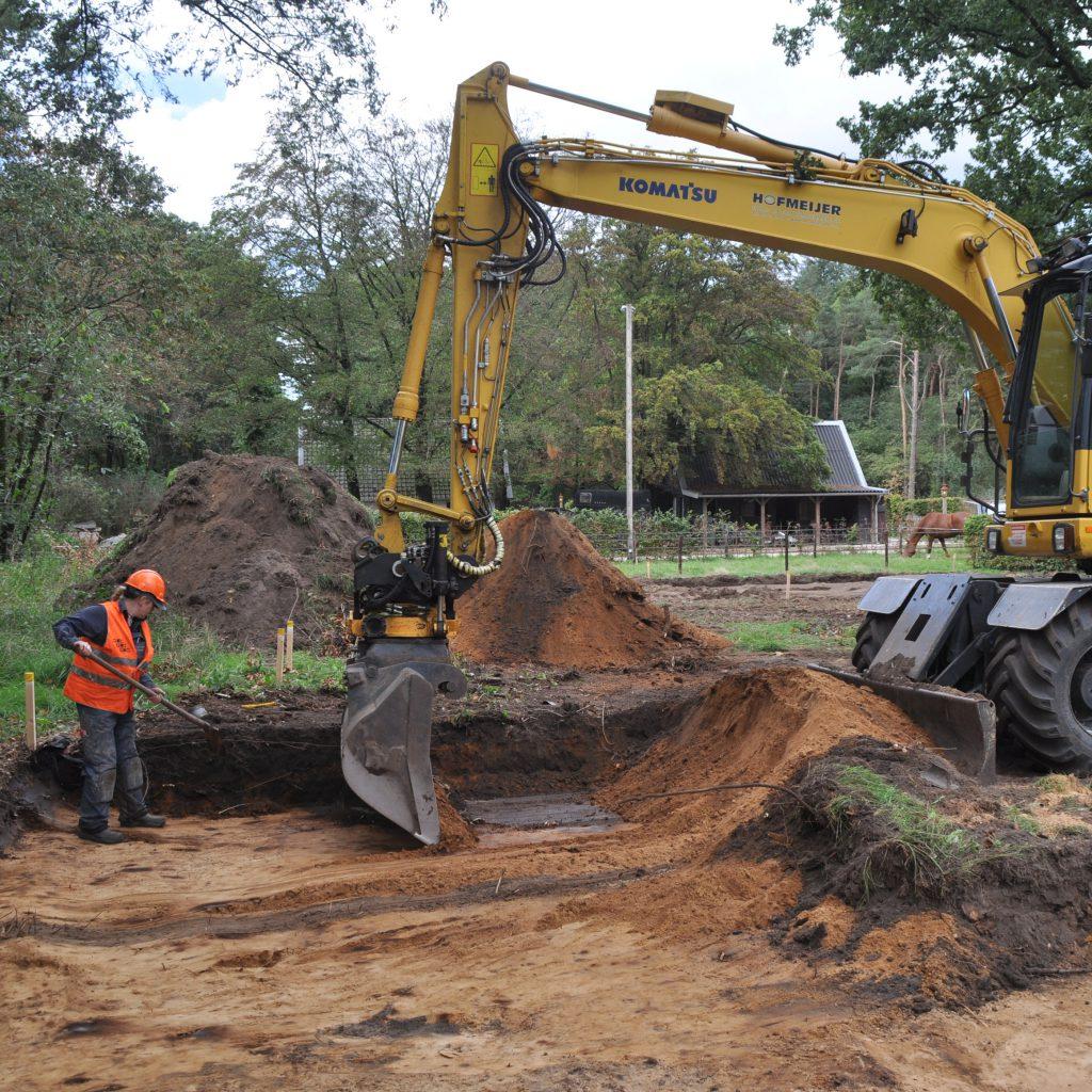 De archeoloog werkt bij het graven van proefsleuven vlak naast de graafmachine.