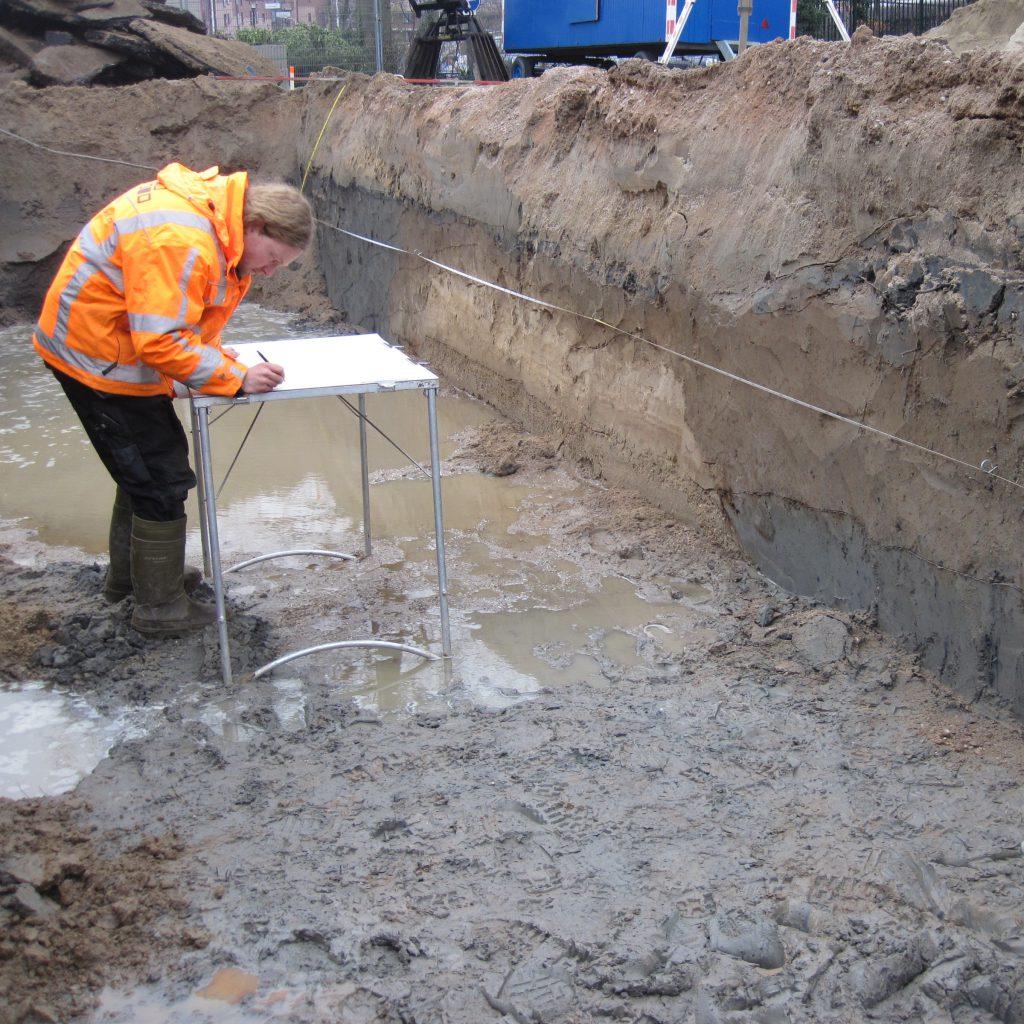 Het tekenen van archeologische sporen in de profielwand bij een proefsleuven-onderzoek.